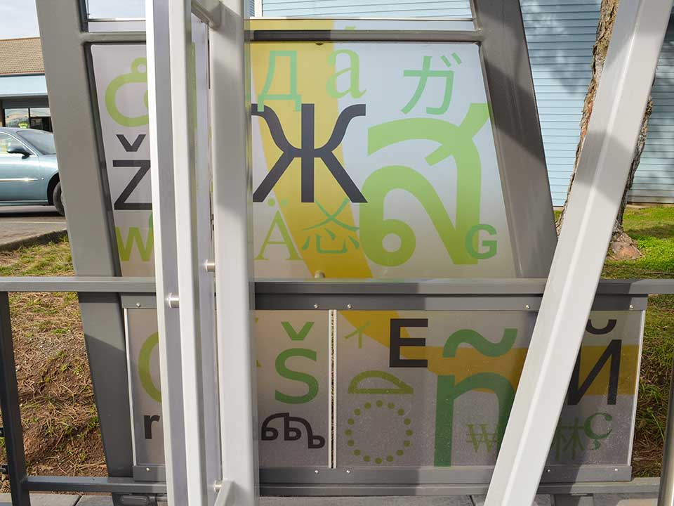 The windscreen includes letters from various alphabets and languages to represent the diversity of Fourth Plain's international corridor. Prominent letters are from the English, Spanish, Russian, Ukranian Thai and Vietnamese languages. Chinese, Japanese, Hawaiian, Punjab, Tibetan and Arabic are also included.