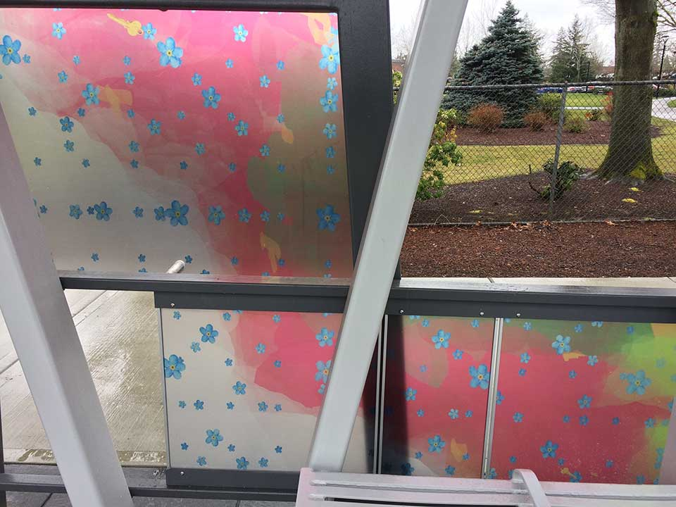 Similar to the Gaiser Hall station, images of flowers and keys symbolize beauty and knowledge against an abstract background of green and contrasting dark colors. The station is located along Fort Vancouver Way near Clark College.