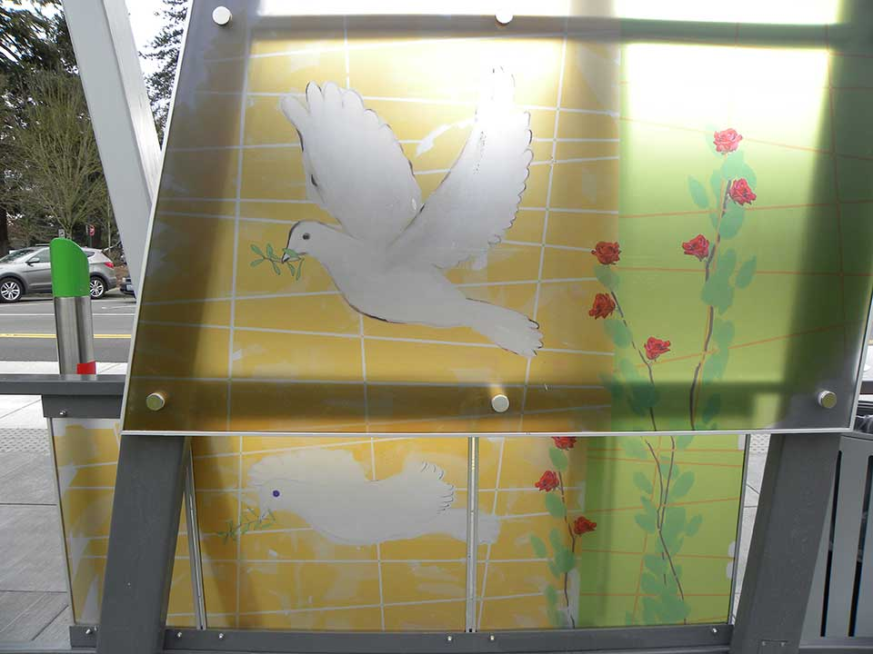 The design uses symbols to represent the two namesakes of the nearby Marshall/Luepke Center. Doves with olive branches refer to George Marshall's winning of the Nobel Peace Prize, and roses are a nod to the Luepke family's longstanding florist business in Vancouver. The flowers and doves go together as symbols of peace.